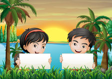 Two smiling kids at the riverbank holding two empty signboards Royalty Free Stock Photography