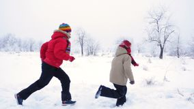 Two kids running together on winter landscape. Two smiling kids running together on winter snow landscape, slow motion 250 fps stock video footage