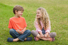 Two smiling kids sitting at park Stock Image
