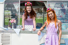 Two smiling ladies wearing vintage dresses with ice cream van royalty free stock photos