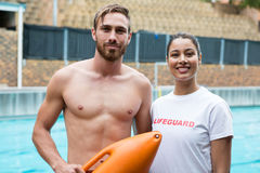 Two smiling lifeguards standing at poolside. Portrait of two smiling lifeguards standing at poolside Royalty Free Stock Images