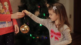 Two smiling little girls decorating Christmas decorations on New Year tree at home. Christmas tree with fir-cone. New. Little girls in comfortable home clothes stock footage
