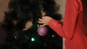 Two smiling little girls decorating Christmas decorations on New Year tree at home. Little girls in comfortable home clothes sitting on floor in beautiful stock video