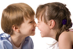 Two smiling little girls sit face to face Stock Images