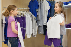 Two smiling little girls trying on the same dress in the store Royalty Free Stock Images