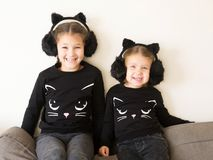 Two smiling little sisters dressed in costumes of black cats. Royalty Free Stock Photos