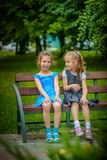 Two smiling little sisters sit on bench Stock Image