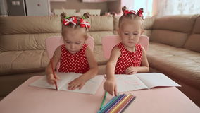 Two smiling little sisters twins draw at the table with colored pencils. stock video