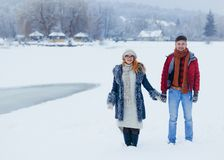 Two smiling lovers are holding hands and joyfully talking during their walk along the countryside full of snow Royalty Free Stock Photo