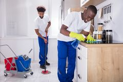 Smiling Two Young Male Janitor Cleaning The Kitchen. Two Smiling Male Janitor Cleaning The Induction Stove And Mopping Floor In The Kitchen stock image