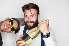 Two smiling man with bottle. Two smiling brunette men with bottle standing against white background looking at camera Royalty Free Stock Photos