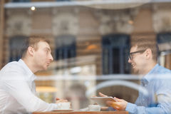 Two Smiling Men Discussing Work Issues in cafe stock image