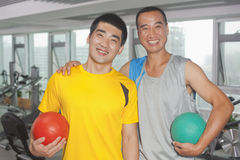 Two smiling men holding balls in the gym Royalty Free Stock Photography