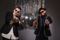 Two smiling men in suits and sunglasses with beer dancing Royalty Free Stock Photography