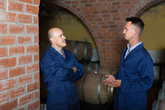 Two smiling men in uniforms standing in cellar with wine woods Royalty Free Stock Images