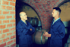 Two smiling men in uniforms standing in cellar with wine woods Royalty Free Stock Image