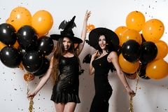 Two smiling models in sexy black outfits are posing with balloons in their hands. Confetti falls on them Stock Images