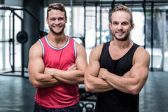 Two smiling muscular men with arms crossed Royalty Free Stock Photos