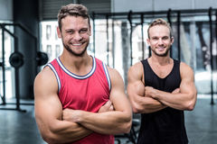 Two smiling muscular men with arms crossed Stock Image