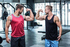 Two smiling muscular men flexing biceps Stock Photo
