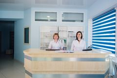 Two smiling nurses working at hospital reception desk stock photos