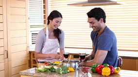 Two smiling people clinking their glasses. In the kitchen stock footage