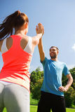 Two smiling people making high five outdoors royalty free stock image