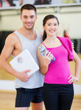 Two smiling people with scale in the gym Stock Images