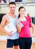 Two smiling people with scale in the gym Stock Image