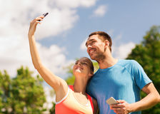 Two smiling people with smartphones outdoors Stock Photos