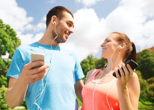 Two smiling people with smartphones outdoors Stock Images