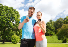 Two smiling people with smartphones outdoors Royalty Free Stock Image
