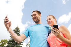 Two smiling people with smartphones outdoors Stock Photo