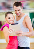 Two smiling people with tablet pc in the gym Royalty Free Stock Photo