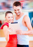 Two smiling people with tablet pc in the gym Royalty Free Stock Photos