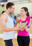 Two smiling people with tablet pc in the gym Stock Images