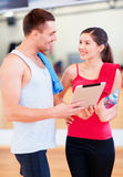 Two smiling people with tablet pc in the gym Royalty Free Stock Image