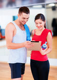 Two smiling people with tablet pc in the gym Royalty Free Stock Images