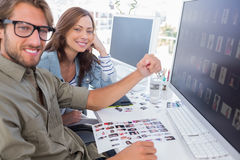 Two smiling photo editors working with contact sheets. And looking at camera Stock Image