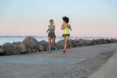Two smiling pretty fitness women running together Royalty Free Stock Images
