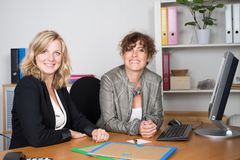 Two smiling pretty young business women in corporate team work sitting on workplace. Portrait of two smiling pretty young business women in corporate team work stock photos