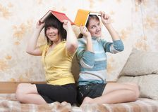 Two smiling reading girls Stock Photos