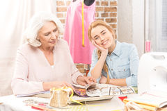 Two smiling seamstresses. Two seamstresses sitting at table and choosing model of clothes to sew stock image