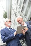 Two smiling senior businessmen working on a tablet standing in front of an office building royalty free stock photo