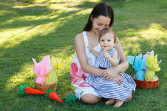 Two smiling sisters: baby and teen girl with chocolate eggs for. Two smiling sisters: baby and teen girl with wicker basket with chocolate eggs for Easter Stock Photography