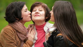 Two smiling sisters are hugging and kissing their mother outdoors. Happy family spending time together in the park. Two Smiling Sisters are Hugging and Kissing stock video