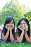 Two smiling sisters lying outdoors Royalty Free Stock Photos