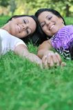 Two smiling sisters lying outdoors in grass Stock Photos