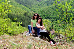 Two smiling sisters in the mountain with their dog Royalty Free Stock Photos