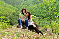 Two smiling sisters in the mountain with their dog Stock Photos